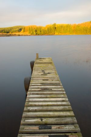 Wooden pier stretching out over a loch in Galloway