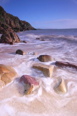 Sea swirling around boulders on a sandy beach in Galloway